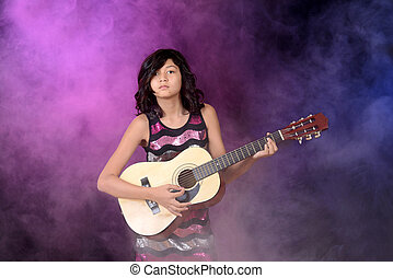 Young girl playing guitar on stage with purple and blue...