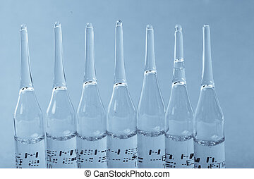 Ampoules with medicine closeup on blue background