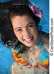 Happy girl in a pool - Pretty teen girl with a fower in a...