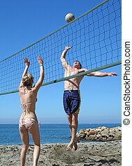 Beach Volleyball - Young people playing volleyball on the...