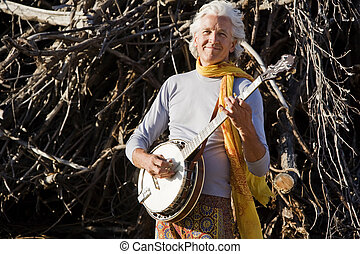 Banjo Player in Front of a Big Pile of Wood