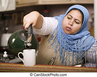 Muslim woman pouring tea - Muslim woman wearing a head scarf...