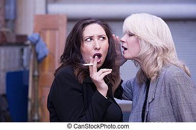 Women Gossip During a Smoking Break - Two women engaging in...