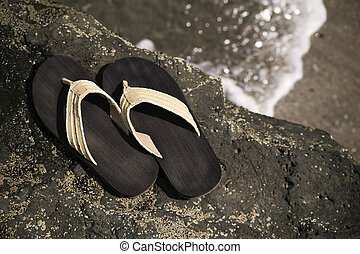 Sandals by the shore - Sandals on a rock with ocean wave in...