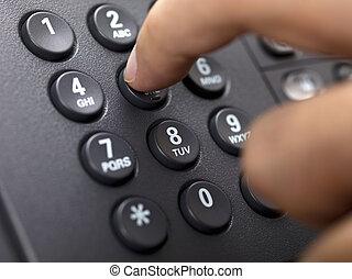 close up shot of human finger pressing landline phone number...
