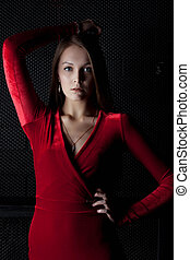 Beautiful young woman in red dress - dark room