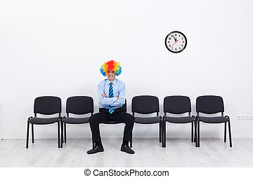 Business as unusual - businessman with clown hair sitting on...