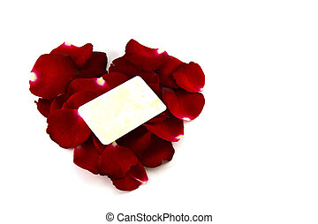 Red rose petals in a heart shape and old card isolated on white background
