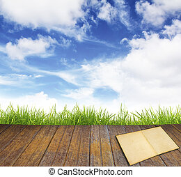 Old book on wood floor with green grass and blue sky