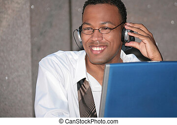 Black Business Man Listening to Music on His Laptop Computer...