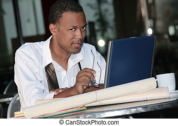 Black Business Man Working Outdoors on a Laptop To Meet a...