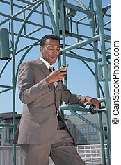 Black Business Man in a Suit Looking At Cell Phone