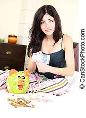 Woman holding money with piggybank happy
