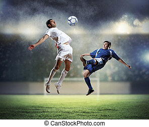 two football players striking the ball - two football...