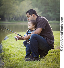 Happy Young Ethnic Father and Son Fishing at the Lake
