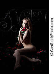 Sexy young woman with rose posing nude in dark - Full length...
