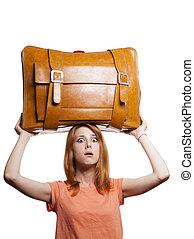 Redhead girl with heavy old suitcase