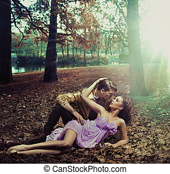 A loving couple lying on autumn leaves - A loving young...
