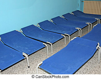 Blue camp beds and little beds for sleeping in a dormitory...