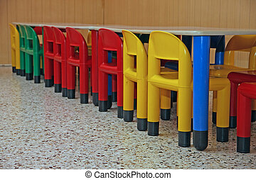 colored plastic chairs and a table in the refectory of the...
