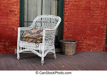 White wicker chair on rustic porch