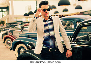 Attractive man wearing jacket and shirt with old cars -...