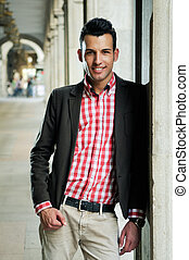 Handsome man wearing jacket and shirt in urban background -...