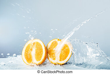 Slices of orange thrown water - Halves of orange thrown...