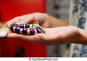 Hands of woman taking a bracelet in a jewelry store -...
