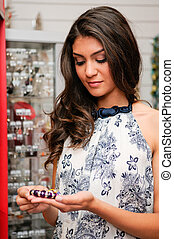 Attractive young woman buying a bracelet at a jewelry -...