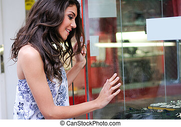 Attractive young woman looking at the shop window