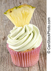 cupcake with mint buttercream and a small piece of pineapple