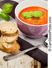 Tasty fresh tomato soup basil and bread on wooden background