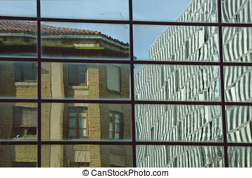 reflection of an old building in a modern glass facade