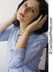 young woman with tattoos wearing headphones and listening...