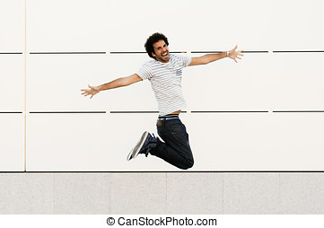 Man with curly hairstyle jumping in urban background -...