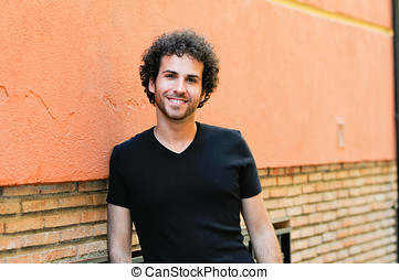 Man with curly hairstyle smiling in urban background -...