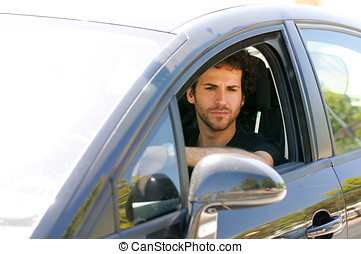 Young man driving a car and looking in the rearview mirror -...