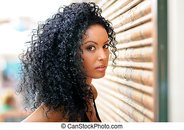 Young black woman in urban background - Portrait of a young...