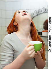 red-haired teen girl gargling throat in bathroom