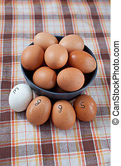 Eggs - Brown eggs in blue bowl and a group of white and...