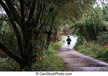 Woman runner running in autumn forest - Portrait of a woman...