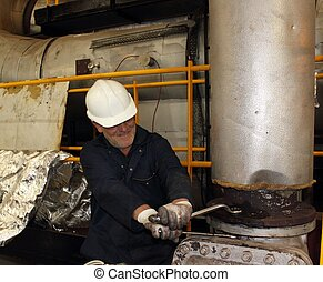 engineer working on a steam valve - An engineer working on a...