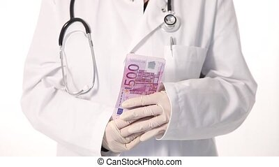 Doctor playing with lots of cash - Cropped view of the...