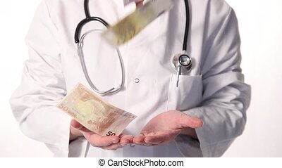 Doctor catching hands full of money - Doctor in a labcoat...