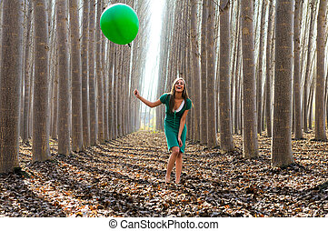 Beautiful blonde girl, dressed in green, laughing in the...