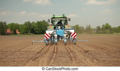 Tractor planting maize - Farmer in a tractor planting maize...