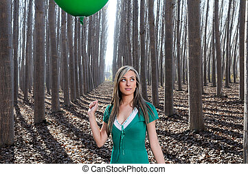 Beautiful blonde girl, dressed in green, standing in the...