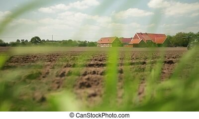 Tractor sowing on ploughed agricult - View through grass of...