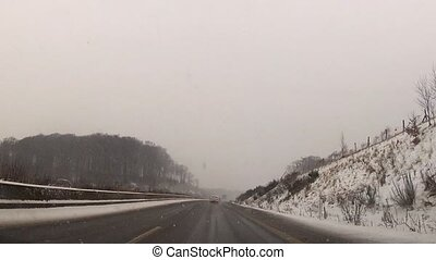 Snowstorm on a rural highway - View from a vehicle of a...
